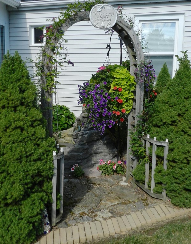 Larry made the arbor for this corner garden that sits next to their sunroom where they relax and listen to singing birds playing in the water. There are two 'Jackmanii' clematis on the arbor, several hostas, and two Alberta spruces for seclusion.