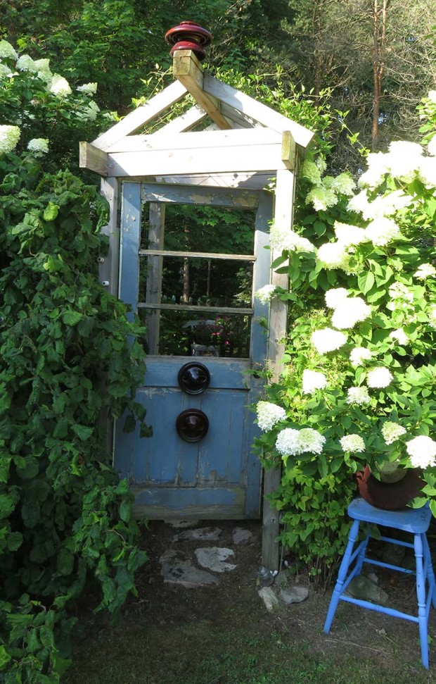 A door opens into the insulator garden and is framed by 'Limelight' hydrangeas.