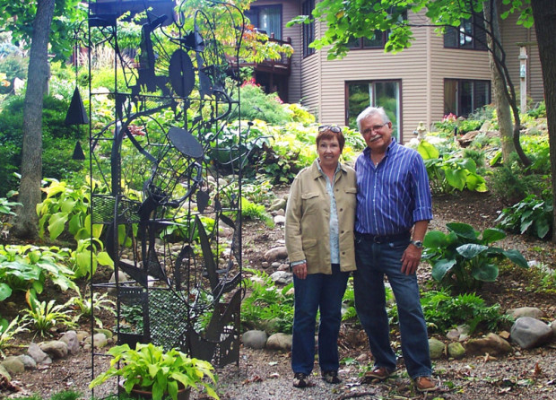 "Kay and Michael Maitner stand in the woodland garden next to a metal sculpture titled ""Kinetic Mandala"" by Steven Spiegel."