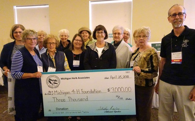 Members of Shoreline Herbarist present a ceremonial check for the Michigan 4-H Foundation to Norm Lownds, right, curator of Michigan 4-H Children's Gardens. The group helped raise funds at the convention through participating in the silent auction and herbal plant sale.