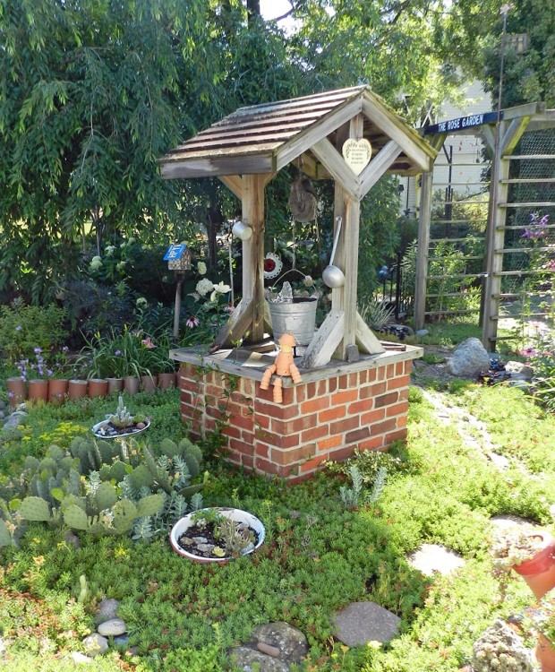 Larry made the wishing well from an old barbeque grill. The arbor Larry also made is covered with clematis, while clay drain tiles serve as a border. Insulators line the paths to keep hoses out of the gardens and prickly pear cactus (Opuntia humifusa), hardy in Michigan, surrounds a planted cactus dish garden.