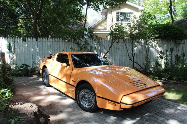 Bob's vintage, orange Bricklin car is parked near the barn where a horse and carriage once resided.