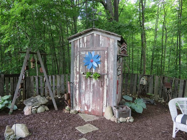 Elaine wanted on outhouse shed, so Roy built one. In the winter, it is a storehouse for the garden's statuary.